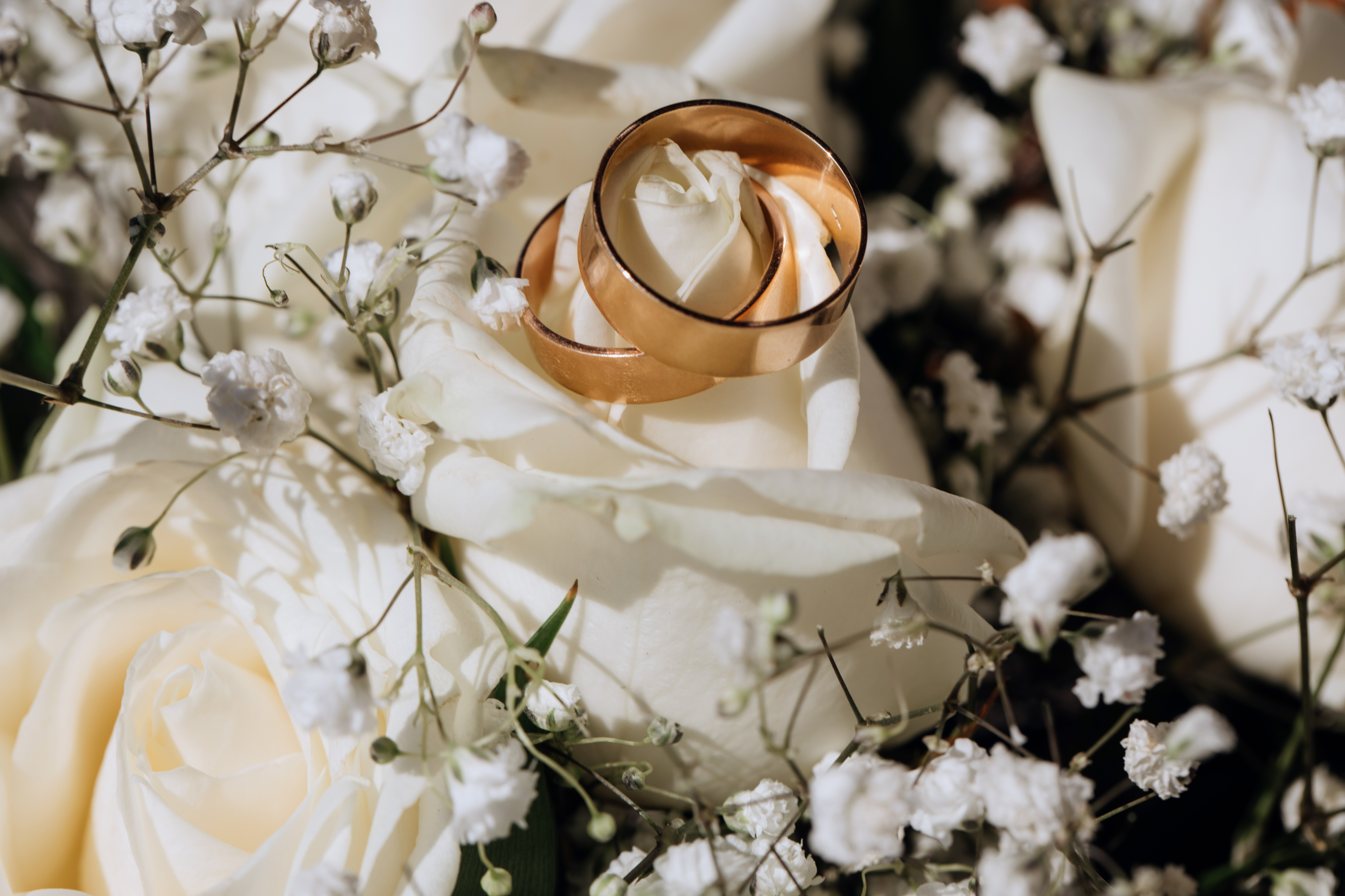 golden-wedding-rings-white-rose-from-wedding-bouquet