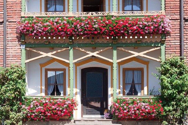Dom s balkónom s dreveným zábradlím a množstvom kvetov