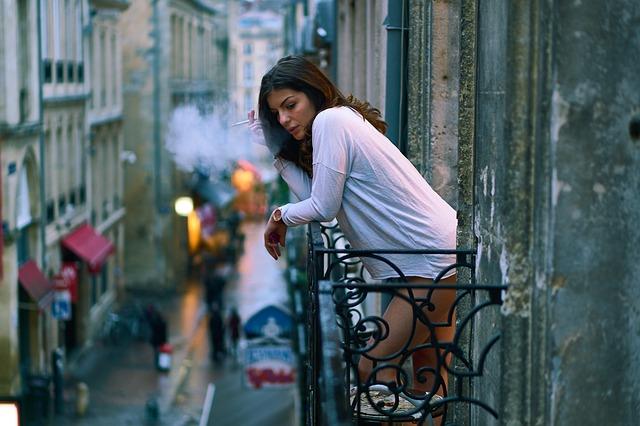 Žena v bielom tričku fajčí na balkóne a opiera sa o zábradlie