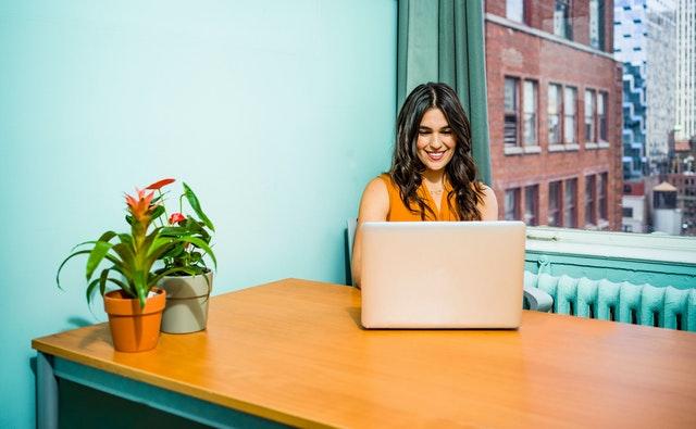 Žena sedí v kancelárii pri okne a píše na notebooku