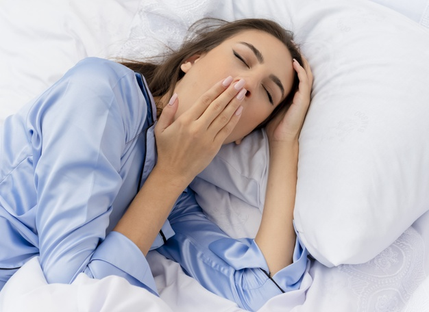 young-beautiful-woman-blue-pajamas-laying-bed_141793-47070